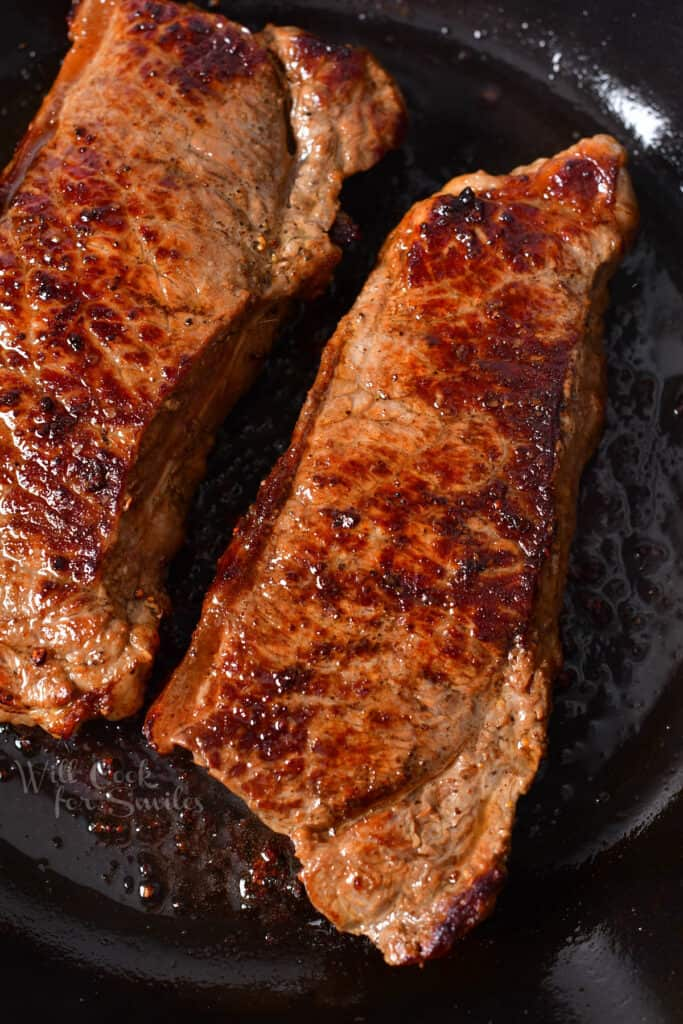 overhead: two new york strips with a brown crust