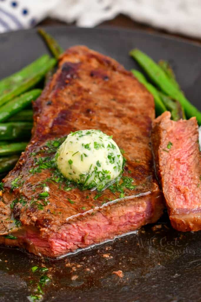 cast iron steak with the end sliced off surrounded by green beans