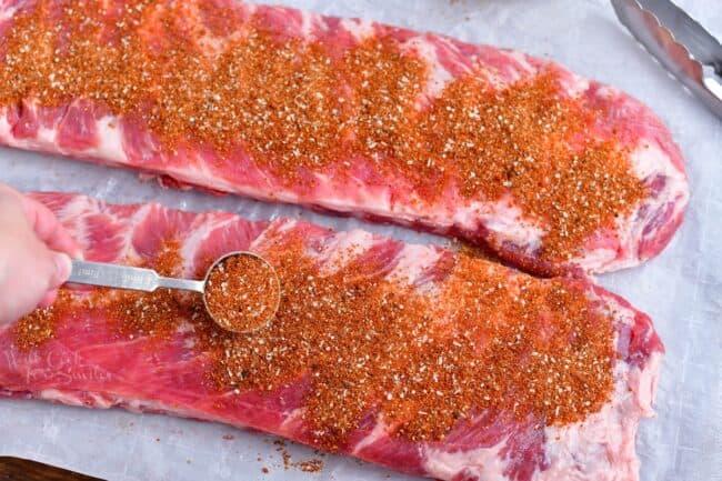 applying dry rub for pork onto rack of ribs before baking