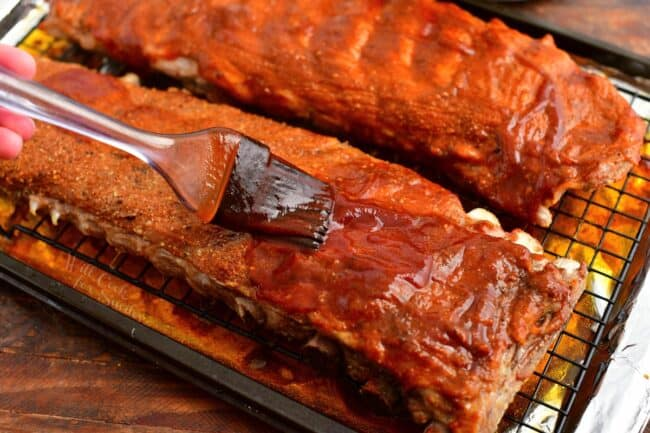 brushing bbq sauce onto two racks of pork