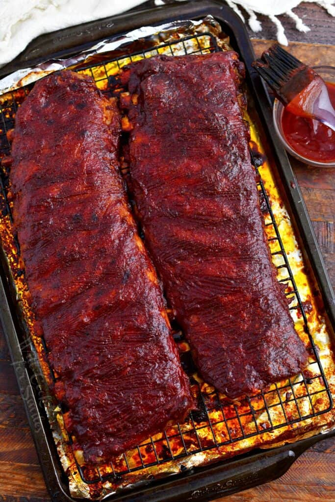 two racks of oven baked ribs brushed with sauce