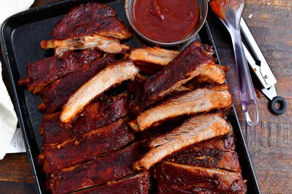 baked pork ribs on serving tray with BBQ sauce