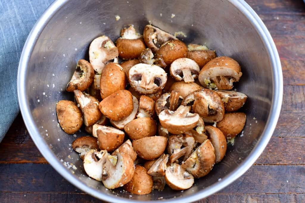 seasoned mushroom slices in metal mixing bowl