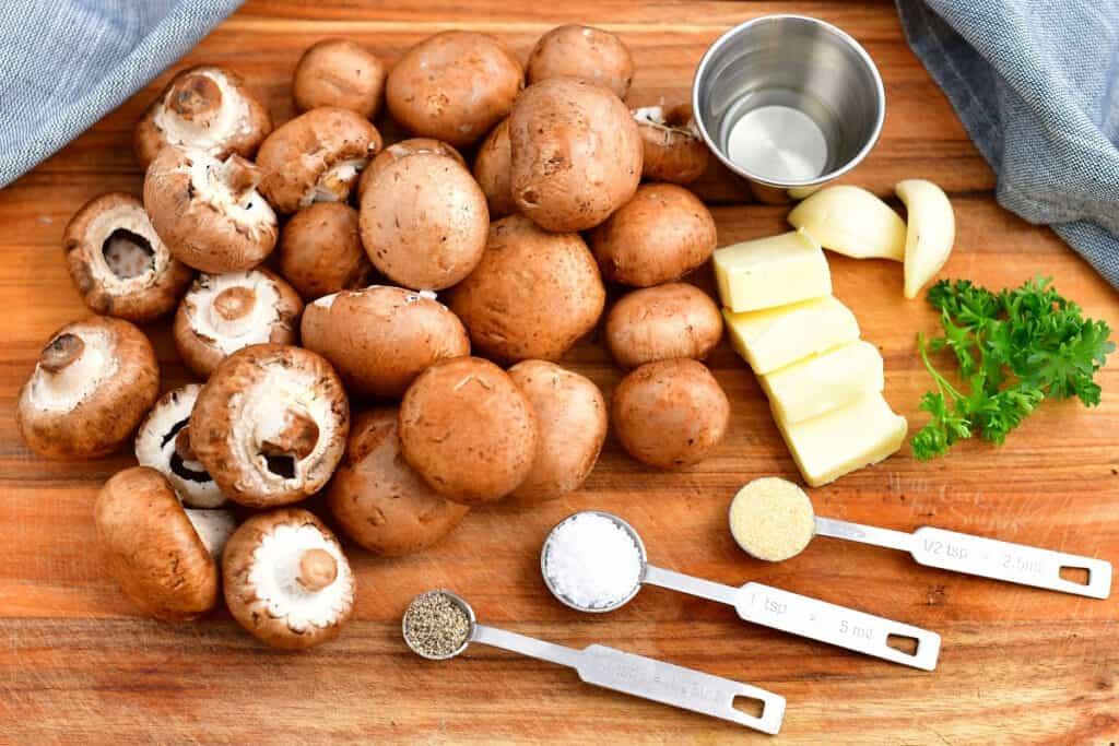 clean cremini mushrooms, butter, parsley and seasonings on cutting board
