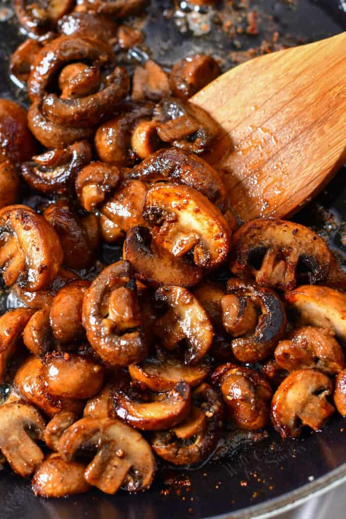 stirring sauteed mushrooms with wooden spoon in a skillet