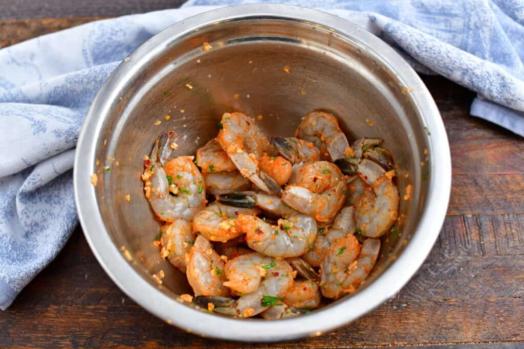 tossing raw shrimp with seasoning in mixing bowl for an easy shrimp recipe