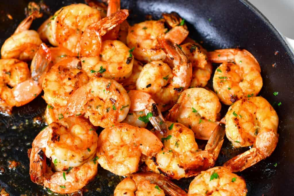 tail-on shrimp sauteeing in skillet