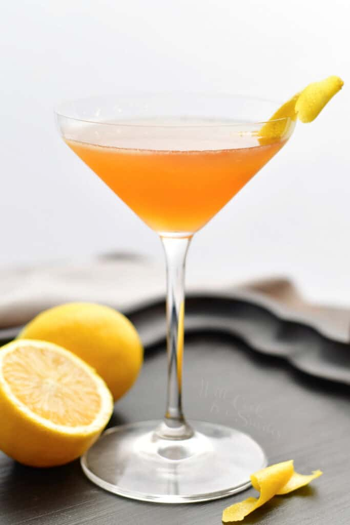 side view of a tall martini glass with orange colored Sidecar cocktail