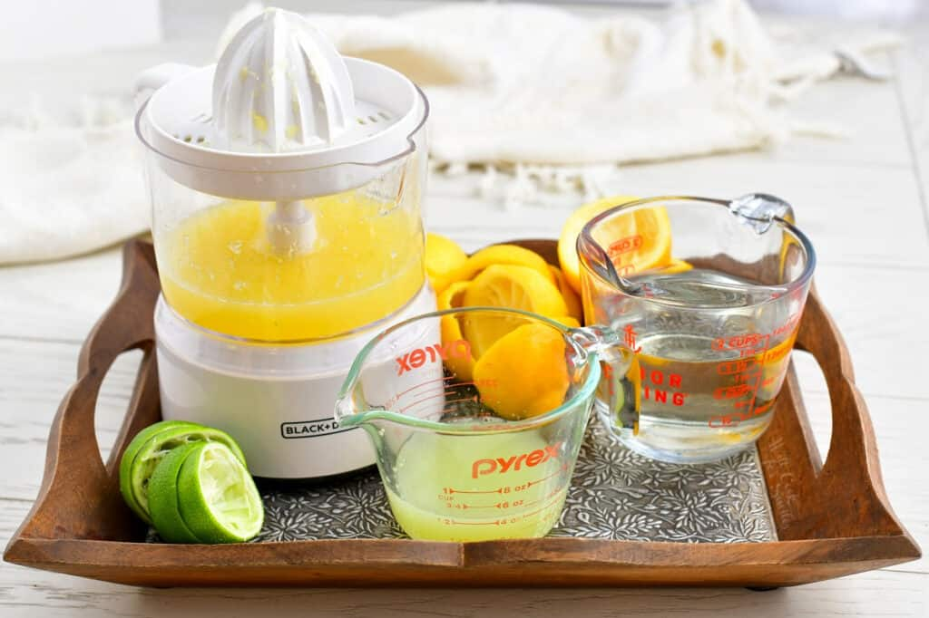 freshly squeezed citrus juice and a measuring cup of simple syrup