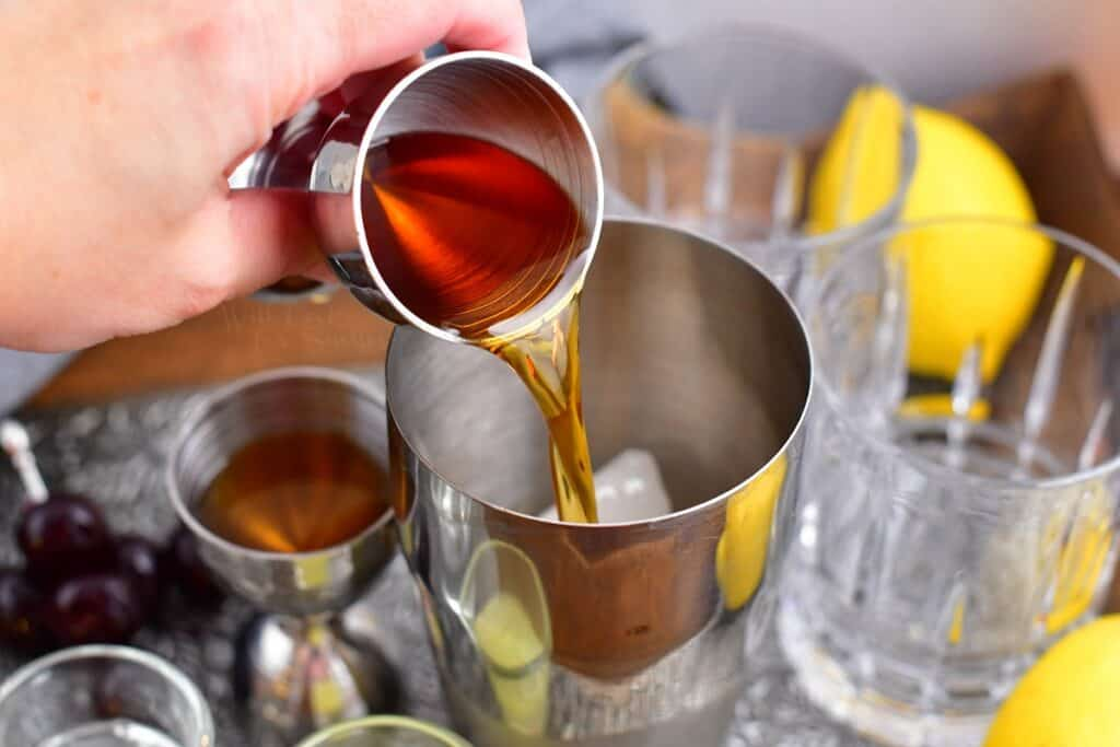 A dark liquor is being poured into a metal cocktail shaker.