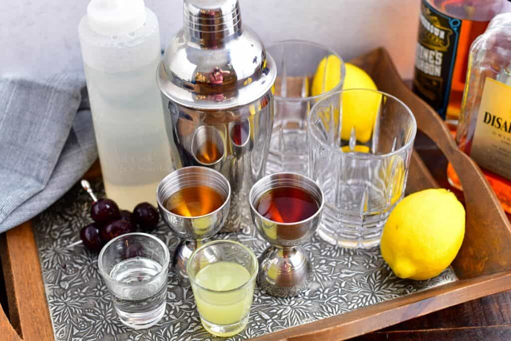 The ingredients for amaretto sour are spread out on a metal surface.