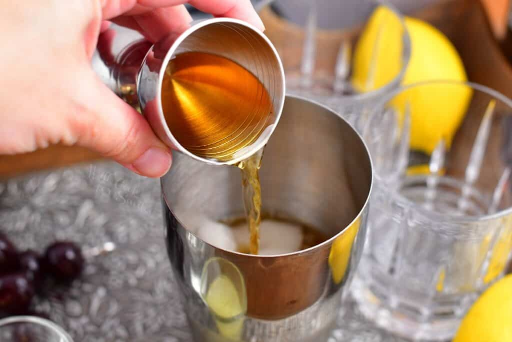A lighter liquid is being poured into the cocktail shaker.