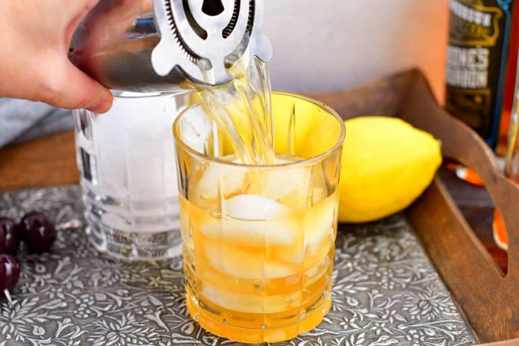 An amaretto sour has been shaken, and is now being poured through a cocktail strainer into a glass half filled with ice.