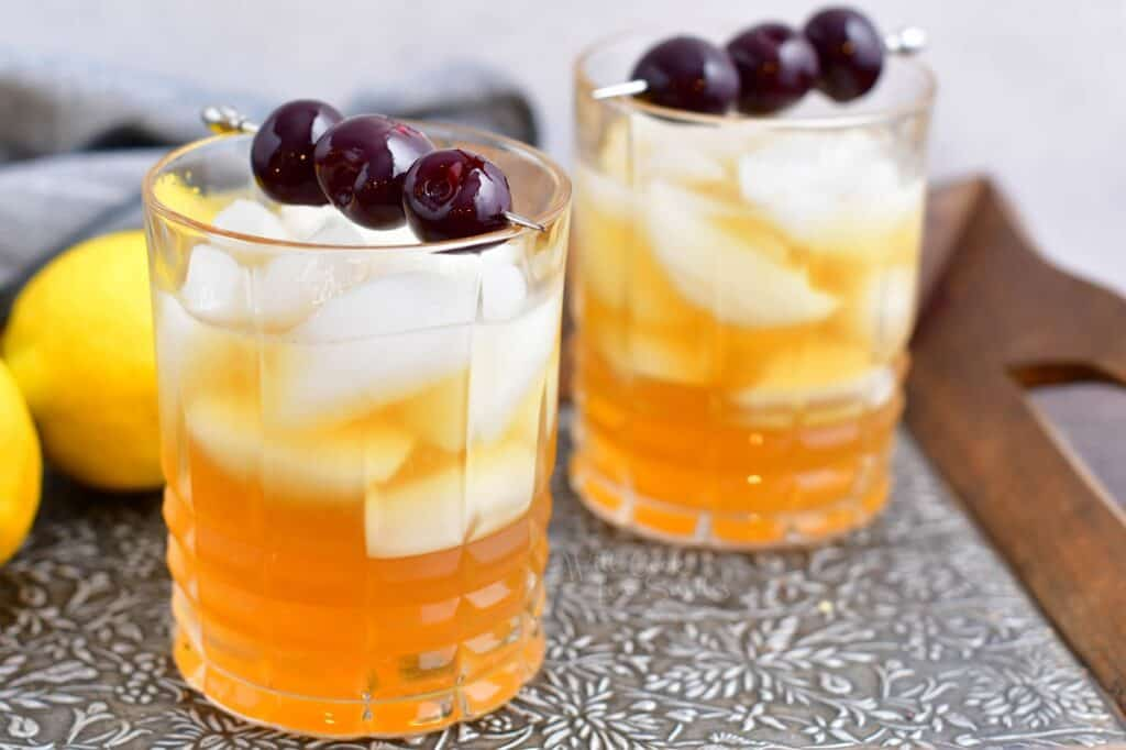 To amaretto sours are placed on a metal surface.
