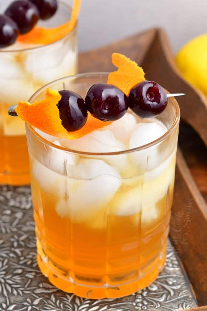 Three olives on a toothpick and an orange peel garnish an amaretto sour.