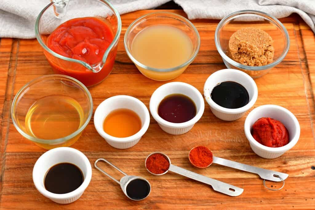 The ingredients for homemade BBQ sauce are presented on a wooden surface.