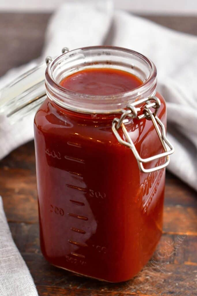 A jar of barbecue sauce is placed on a wooden surface.