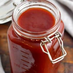 An open mason jar is filled with red BBQ sauce.