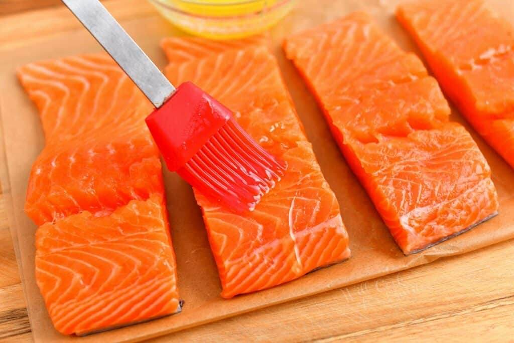 brushing salmon filet with melted butter