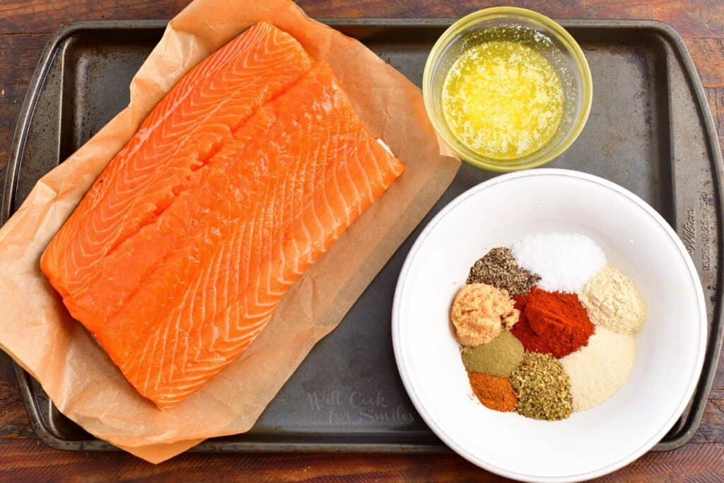 salmon, seasoning, and melted butter on a baking sheet