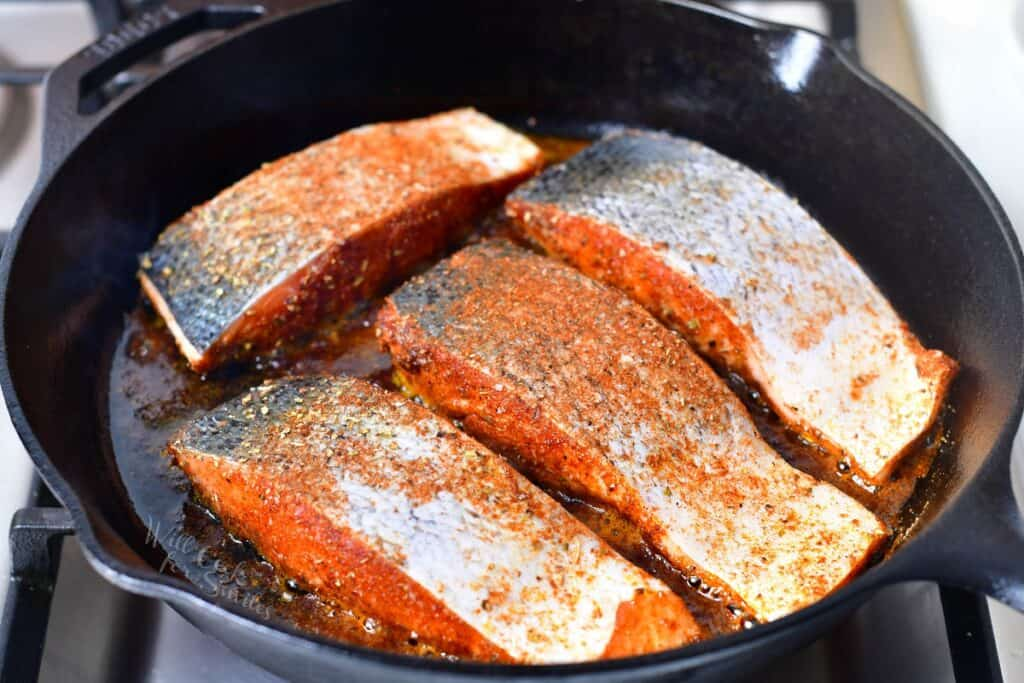 seasoned salmon fillets in a skillet on a stove