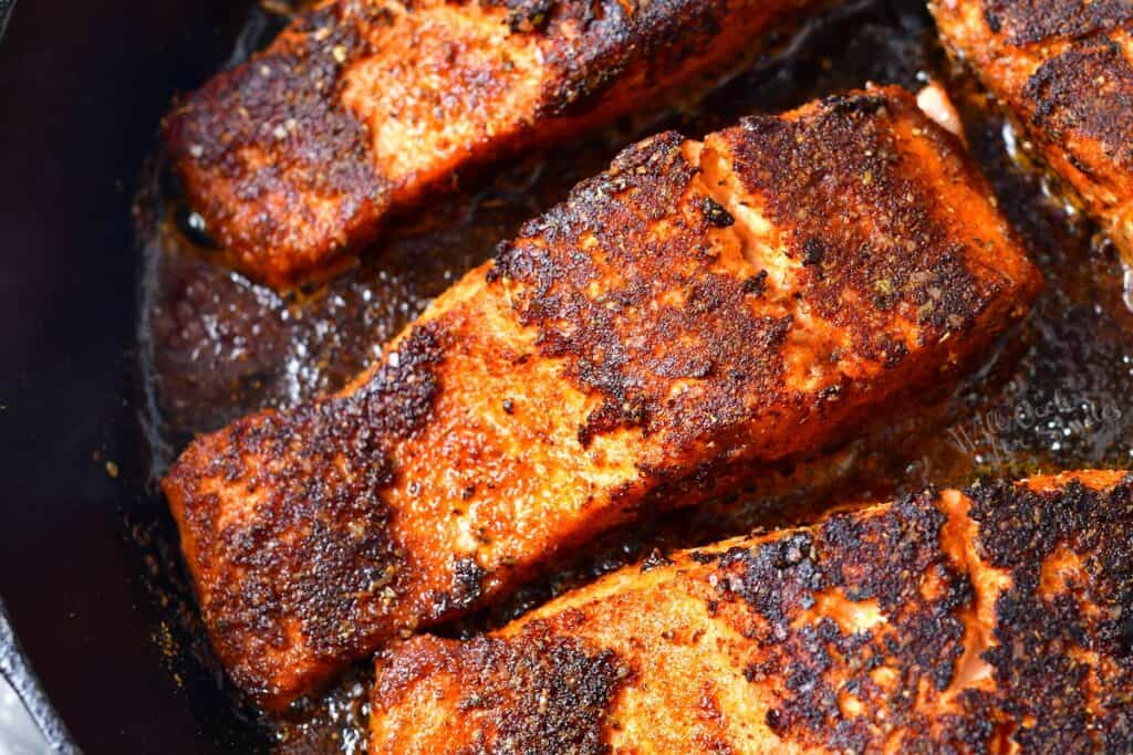 closeup of salmon seasoned and cooking in a skillet