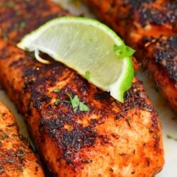 closeup of blackened salmon filet with a lime wedge