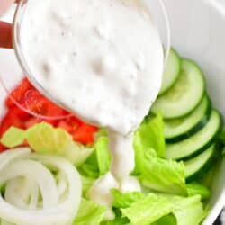 Blue cheese dressing is being poured on to a salad.