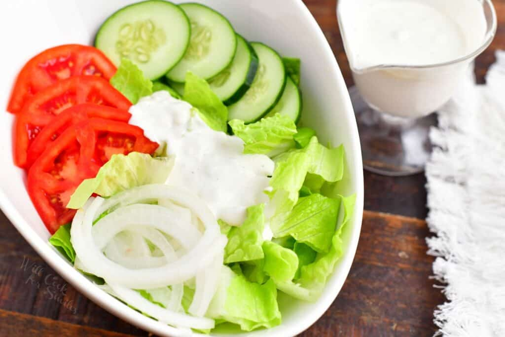 A small amount of blue cheese is drizzled on a chopped salad.