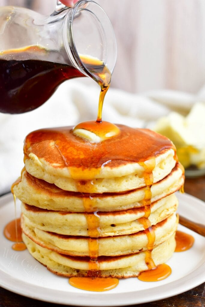 Maple syrup is being poured over a stack of buttermilk pancakes.