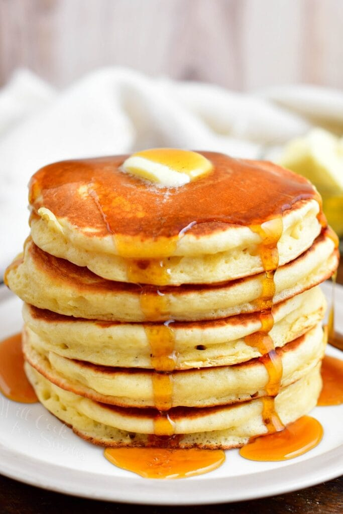 A stack of buttermilk pancakes is presented on a white plate with butter and syrup.