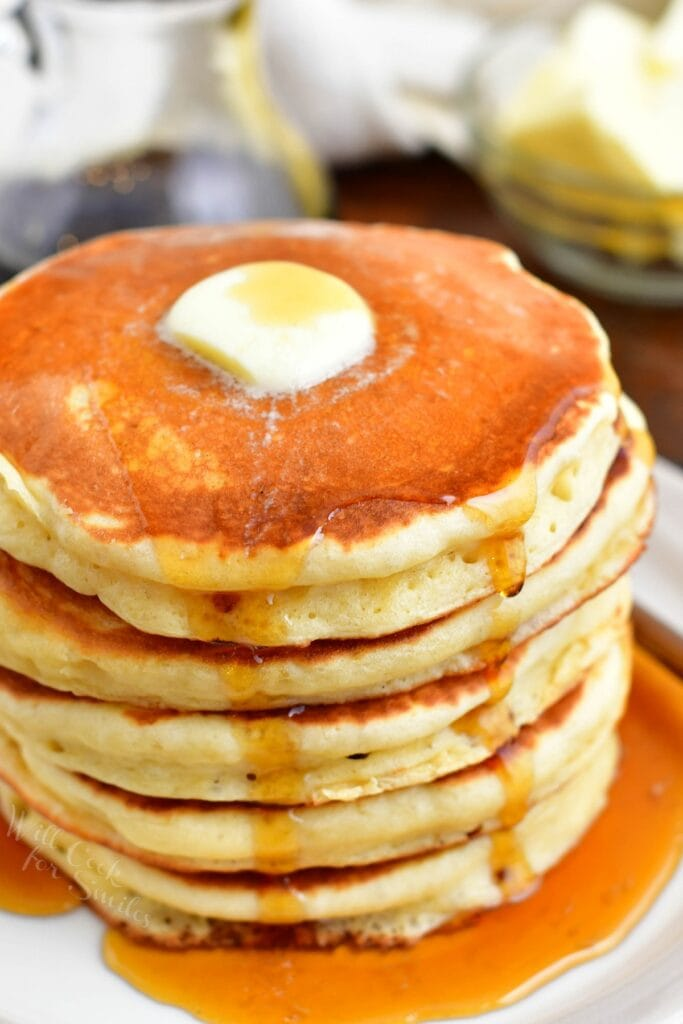 A stack of buttermilk pancakes is topped with a square of butter and drizzled with maple syrup.