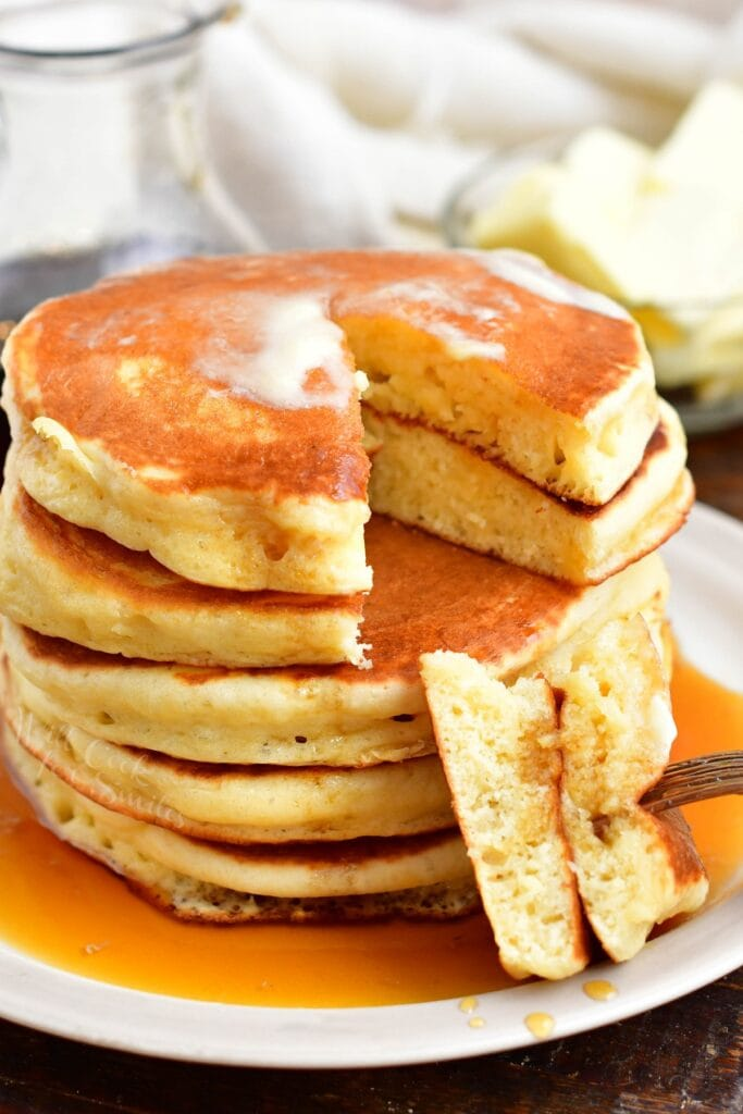 A bite sized portion of pancakes has been taken from the stack.