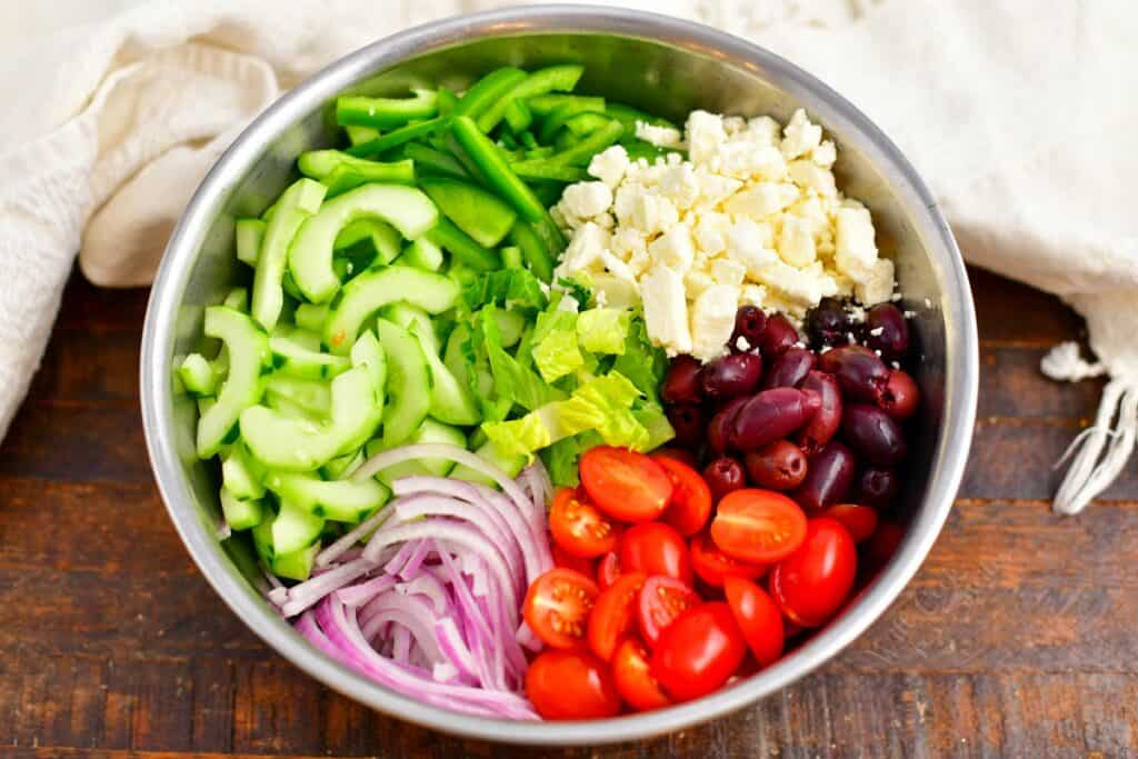 The ingredients for greek salad are all placed in a large silver mixing bowl.