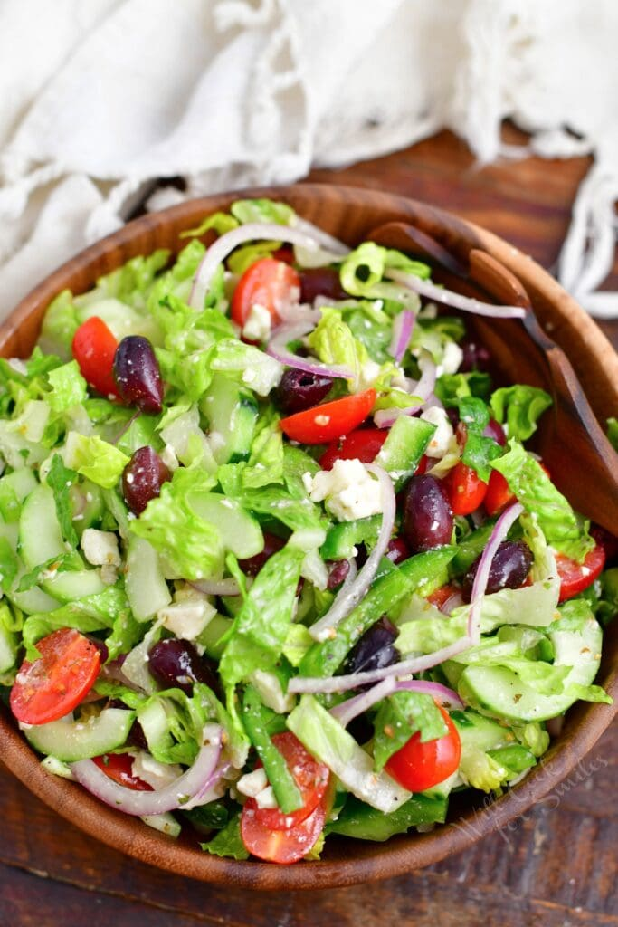 A tossed greek salad is in a large wooden bowl.