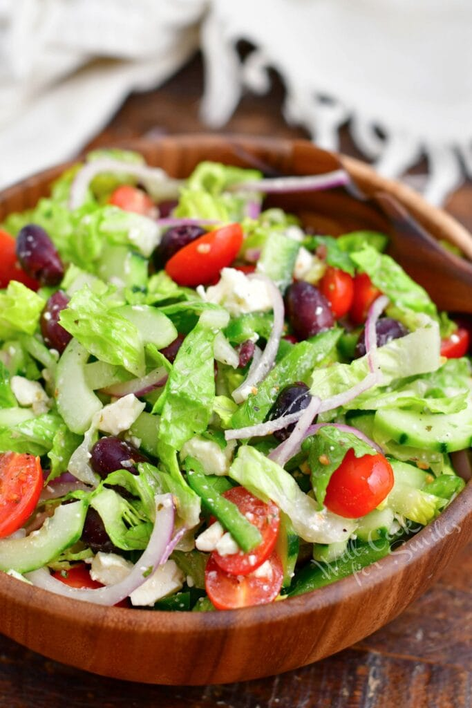 A greek salad in a large wooden serving bowl has been tossed and is ready to be served.