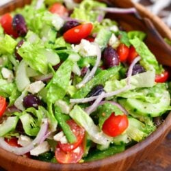 A freshly made greek salad is in a wooden bowl with a large wooden serving spoon.