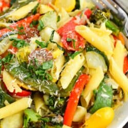 A white plate contains a large portion of pasta primavera.
