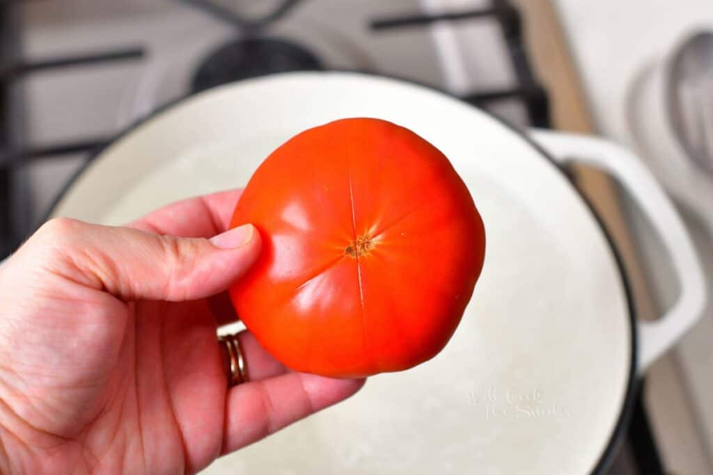 holding fresh tomato with a x cut on a bottom