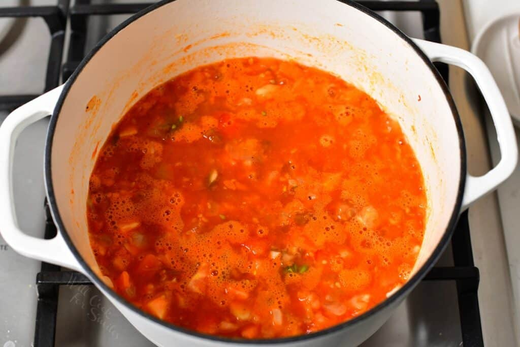 simmering tomato sauce in a white Dutch oven