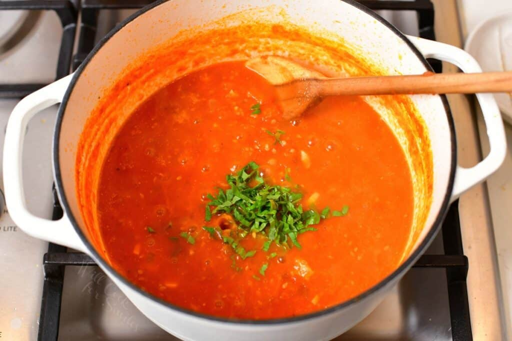 cooked tomato sauce in a white pot with fresh basil added