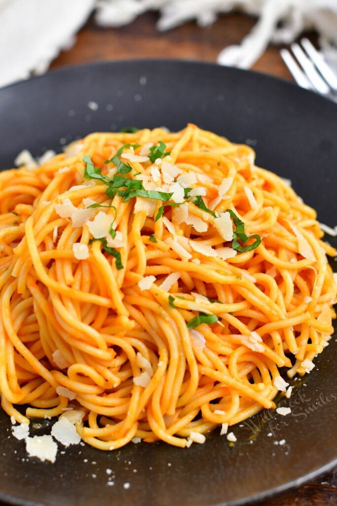 spaghetti coated in Pomodoro sauce on a dark plate with Parmesan and basil