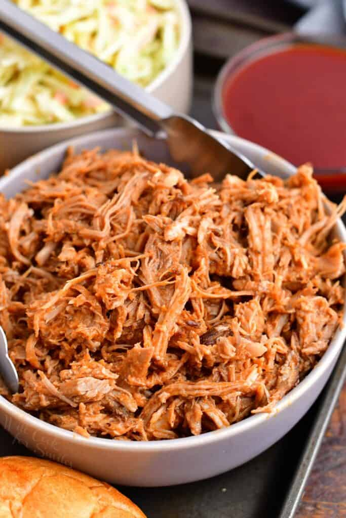 Pulled pork is placed in a white bowl.