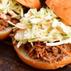 Coleslaw is sitting on a freshly made pulled pork sandwich.
