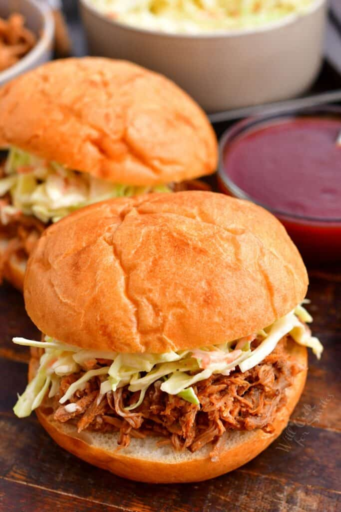 Two pulled pork sandwiches are placed next to each other.