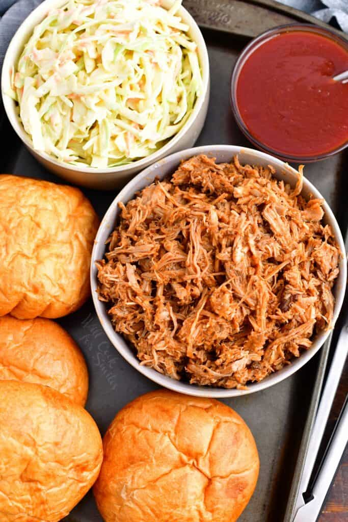 The ingredients for pulled pork sandwiches are presented on a metal surface.