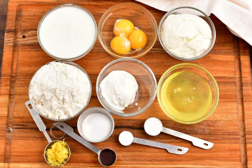 The ingredients for ricotta pancakes are placed on a wooden surface.