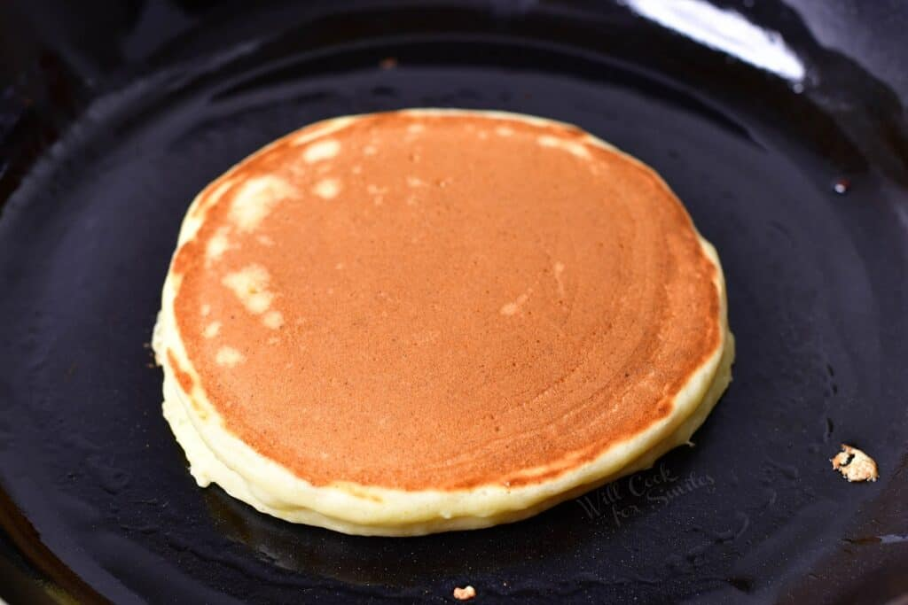 A ricotta pancake has been flipped in a black skillet.