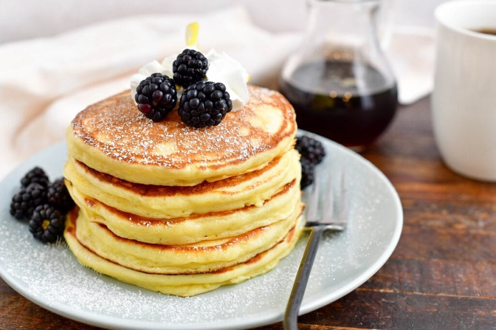 A stack of pancakes is topped with blackberries on a white plate.