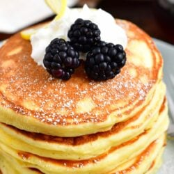 A stack of ricotta pancakes is topped with whipped cream and blackberries.
